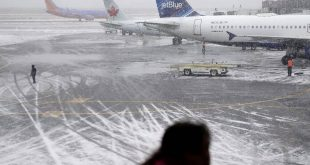 A girl watches activity at LaGuardia Airport in New York, Monday, Jan. 26, 2015.Airlines canceled thousands of flights into and out of East Coast airports as a major snowstorm packing up to three feet of snow barrels down on the region.  (AP Photo/Seth Wenig)